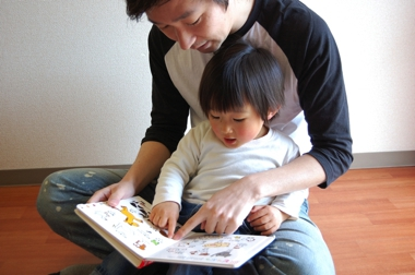 a Japanese father and son reading a book together