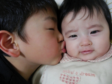 Elder brother kissing his younger baby sibling